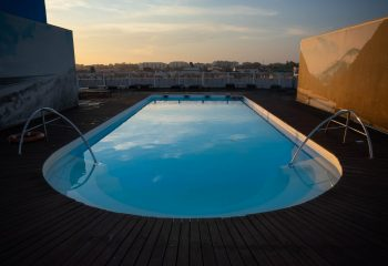 oval swimming pool with wooden pool decks